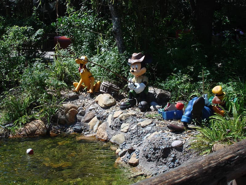 Mickey Mouse fishing statuette near green leaf plant