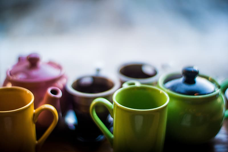 Assorted-color ceramic teapots and cups