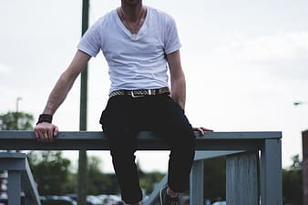 Man in white shirt and black pants sitting on gray fence