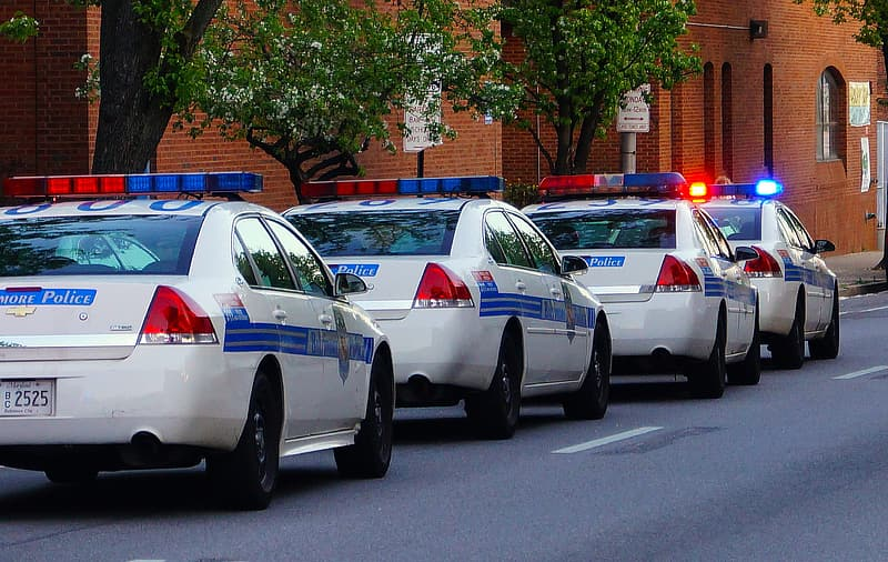 Four white police cars on road