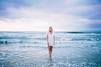 Woman in white long sleeve dress standing on sea water under white clouds during daytime
