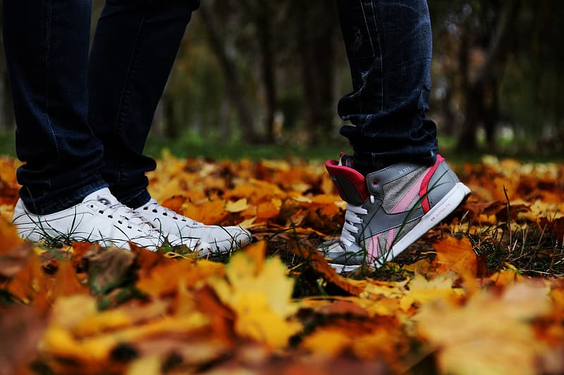 Two people standing on brown leaves
