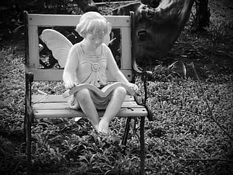 Grayscale photography of fairy statue sitting on bench