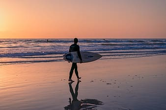 Silhouette photography of man walking on beach while holding surfboard
