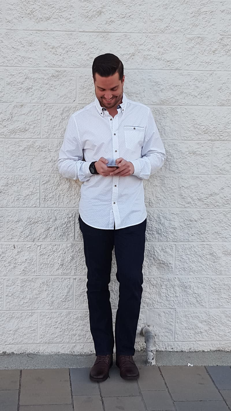 Man using smartphone while standing against the white wall