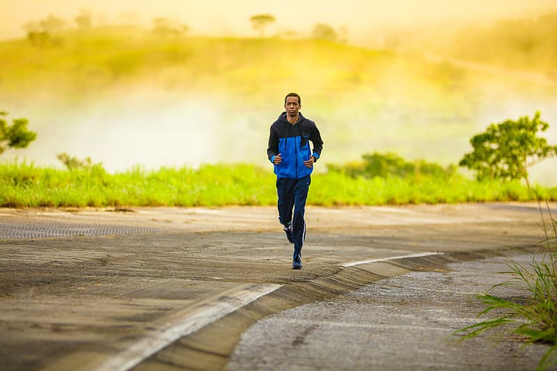Man wearing blue and black jacket and pants running on road