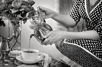 Grayscale photo of person holding teapot