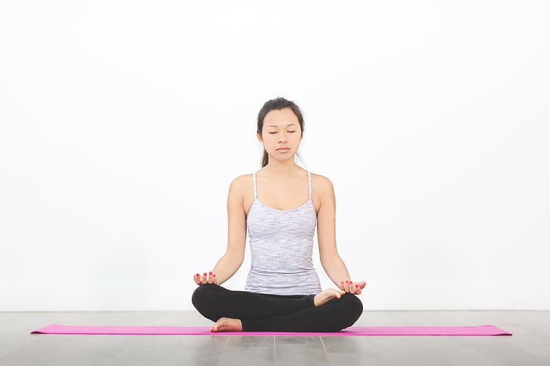 Woman in gray spaghetti strap top sitting on pink yoga mat while meditating