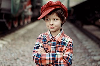Standing boy in plaid long-sleeved shirt with red newsboy hat