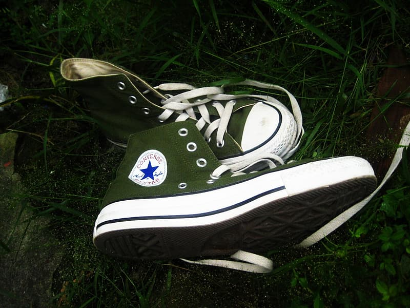 Black and white converse all star high top sneakers on green grass