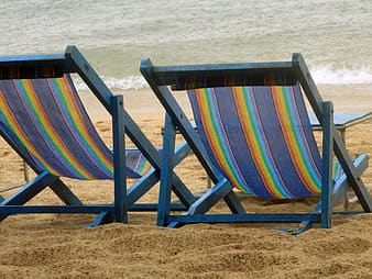 Two blue lounge chairs on brown sand near body of water