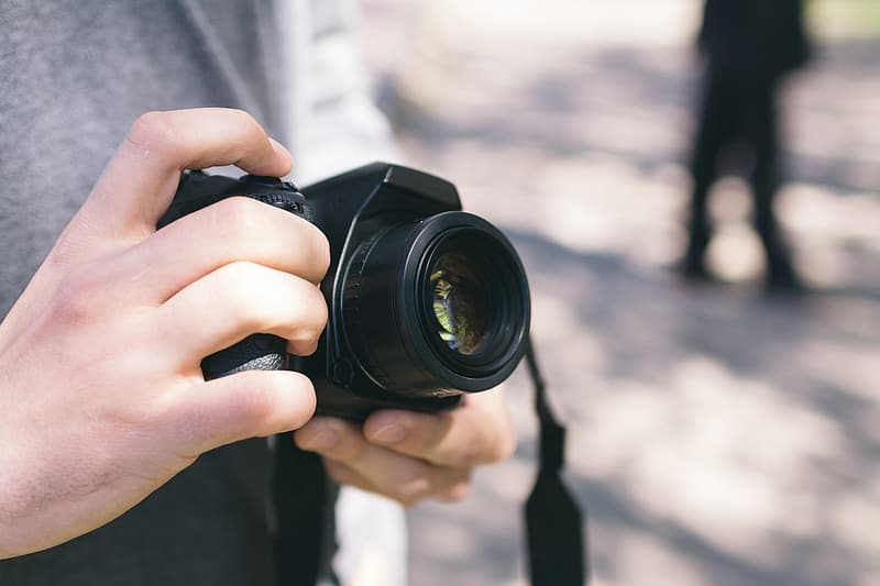 Person holding black DSLR camera during daytime