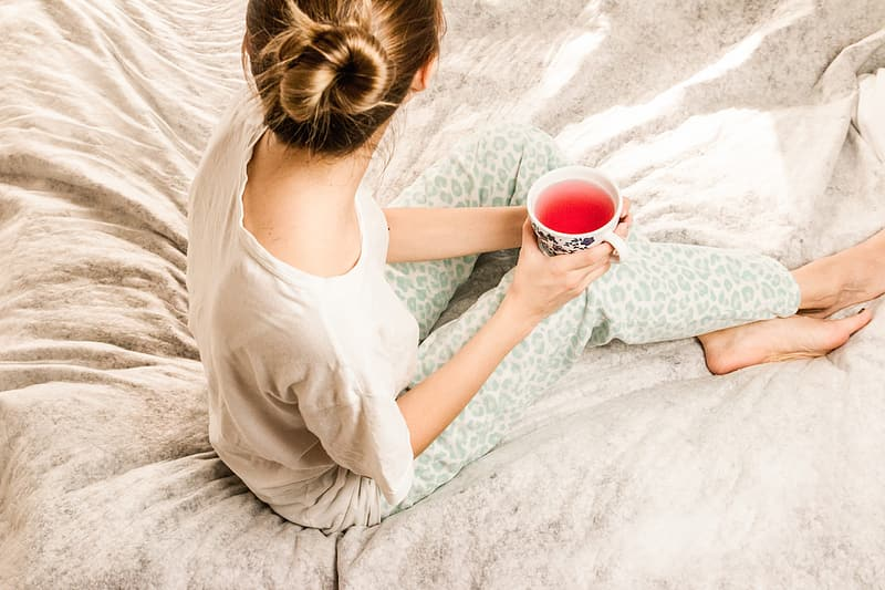 Woman holding white cup sitting on bed