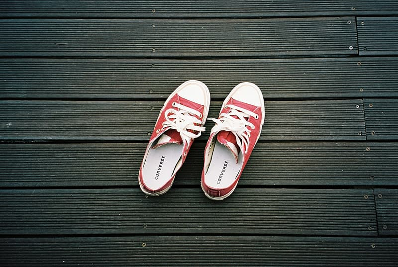 Pair of red-and-white Converse All Star low-top sneakers on gray surface