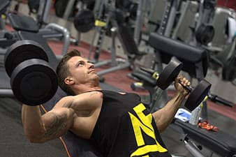 Man in black and yellow nike tank top doing exercise