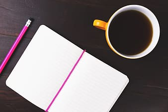 Notepad, notebook, pencil and coffee cup on wooden office desk