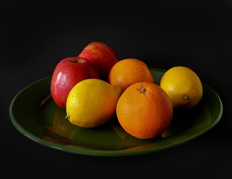 Four orange fruits and two honeycrisp apple fruits on clear glass plate