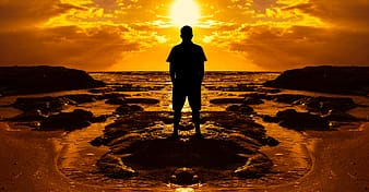 Silhouette of a man standing on rock