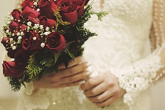 Person's hand holding bouquet of red rose flowers