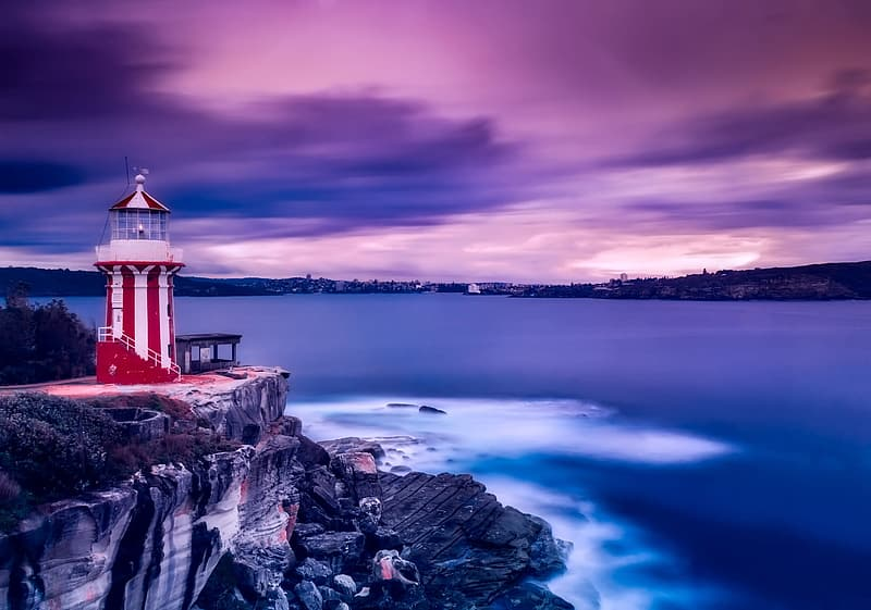 Red and white lighthouse near body of water under cloudy sky
