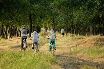 Three persons cycling outdoors