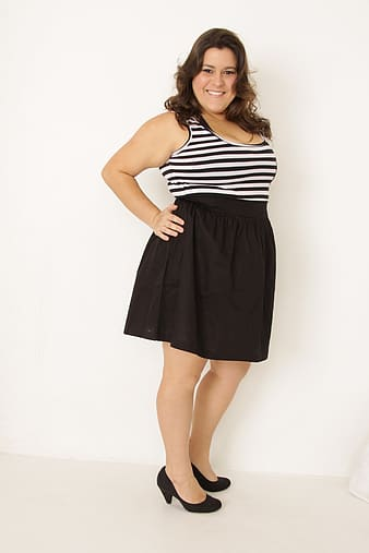 Smiling woman in black and white striped sleeveless mini dress