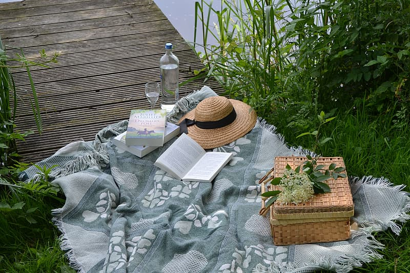 Brown wicker basket and sombrero on picnic table