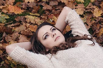 Woman laying on dried leaves photo