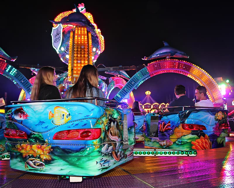 Person riding in amusement park during nighttime