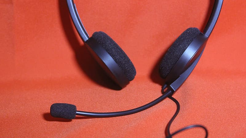 Black corded headset on red surface