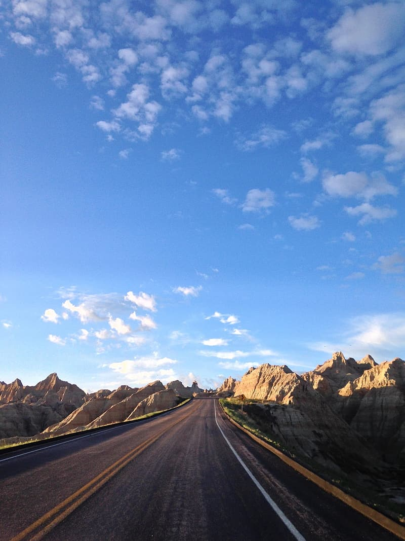 Gray asphalt road between brown mountains under blue sky and white clouds during daytime