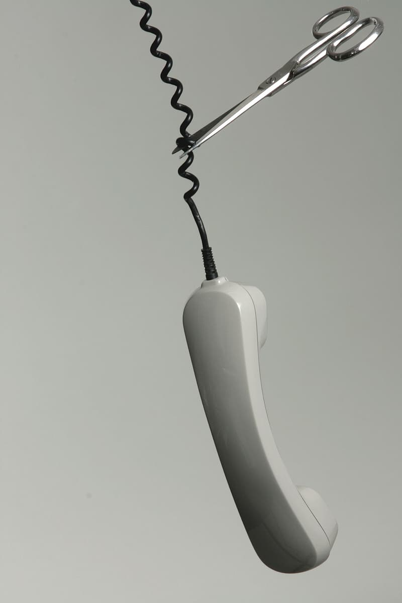 Gray and white telephone cord being cut