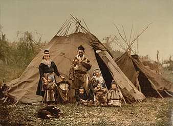 Group of people and children standing near teetee tent