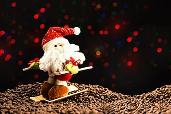 Santa Claus plush toy on top of coffee beans