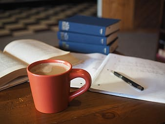 Cup of coffee near click pen and notebook on table