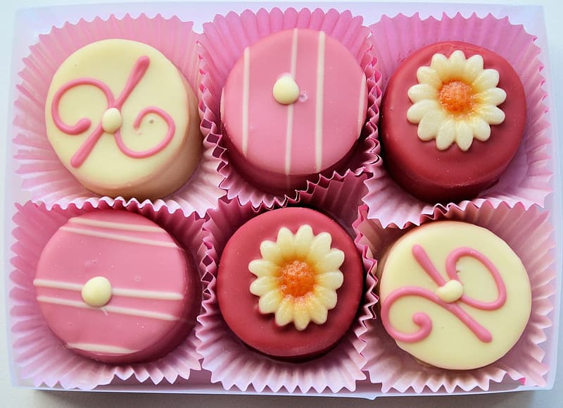 Close-up photo of 6-pieces pink and beige-icing covered muffins