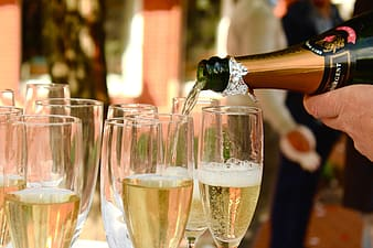 Person pouring champagne in glasses