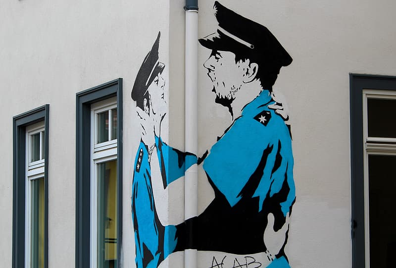 Man in blue jacket and black hat painting