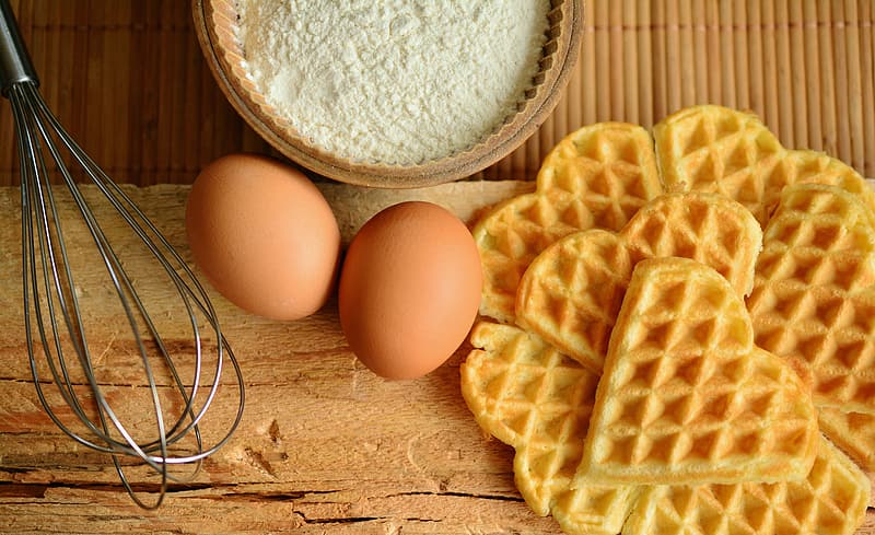 Waffle, eggs, flour and whisk with chopping board