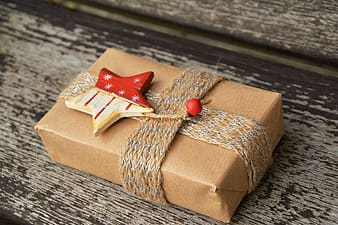 Brown and red gift box on brown wooden surface