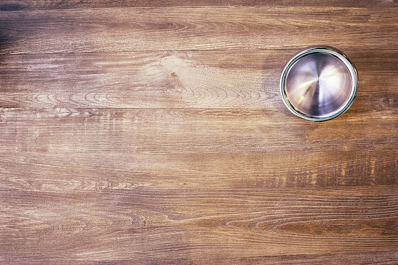 Stainless steel round container on brown wooden table
