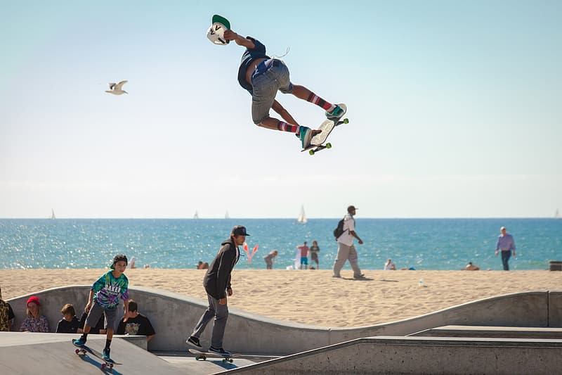 Man in blue shirt and black shorts jumping on brown wooden skateboard during daytime