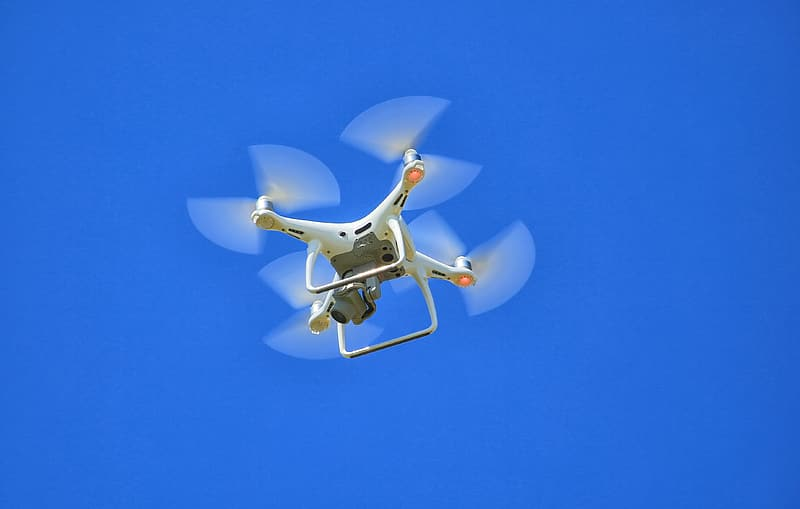 Closeup photo of flying white and orange drone