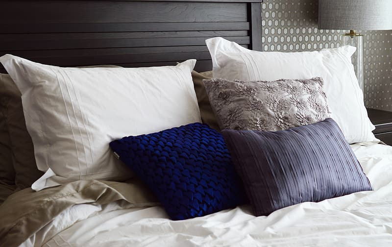 Assorted-color pillows on bed