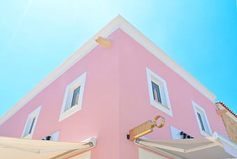Pink and white concrete building under blue sky during daytime