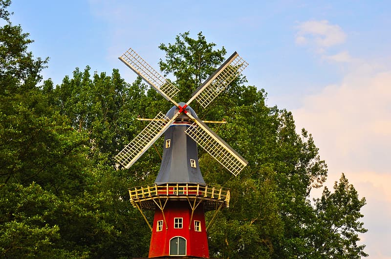 Gray and red windmill near trees