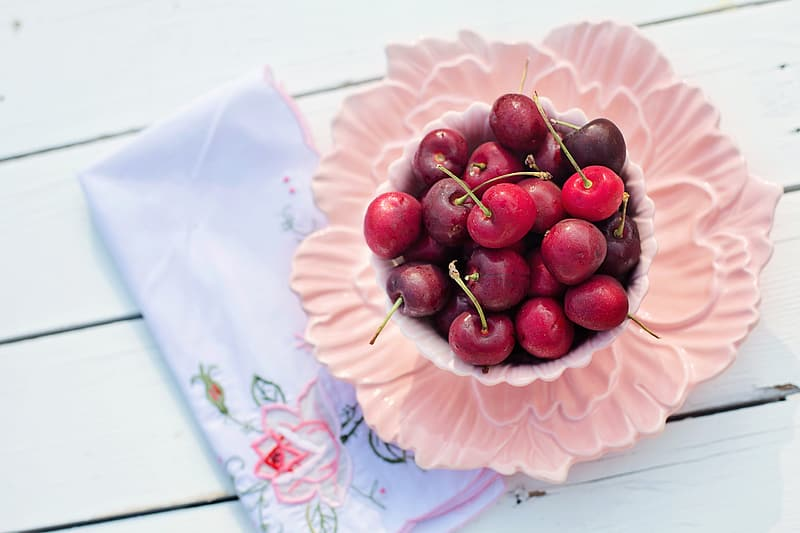Red cherries on pink tray
