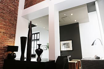 Three black vases on top of black wooden furniture beside white column