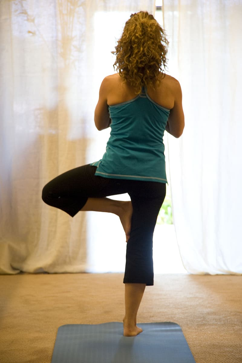 Woman in blue tank top standing on yoga mat