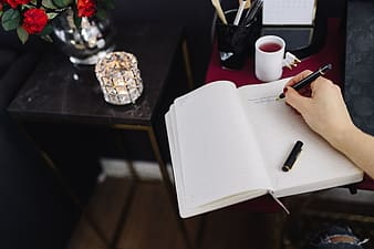 White notebook on brown wooden table